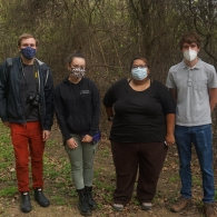 Members of the (Re)claiming Memories Research Lab masked, looking at the camera in the San Jose Cemetery
