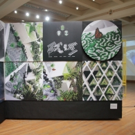View of the OTHER NATURE exhibit from the backside, focused on a two-by-three panel of the exhibition that includes a monarch butterfly, with a video projected on the wall in the background