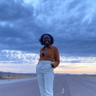 Temi Osanyintolu with her hands in her pockets smiling at the camera, standing in the middle of the road in West Texas, with the sunset in the background
