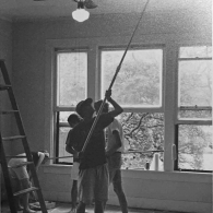 New Guild cooperative residents painting the living room ceiling, Spring 1991.