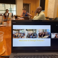 """On a laptop, a presentation reads """"Welcome to Design Futures."""" The laptop sits on a table in the foreground with a cup of tea. In the background three individuals are seen looking at their computers as well."""