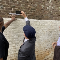 Three men seen looking at a historic wall, measuring fingerprints of enslaved people. Provided by Kathleen Conti to represent her dissertation research.