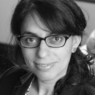 Black and white headshot of Sarah Lopez, wearing glasses, smiling at the camera