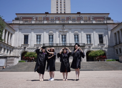 "Four graduates in front of the UT Tower posing in a way that spells ""SOA"""