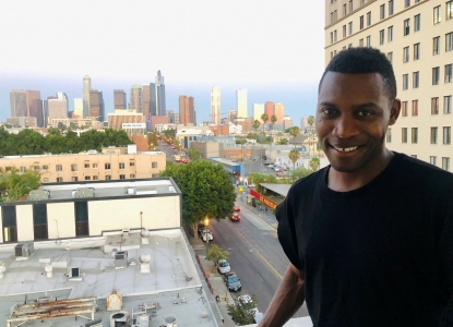 Tekena Koko smiles at the camera as he's standing on a balcony that overlooks an urban skyline at dusk