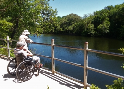 Older couple, one in a wheelchair, looking out onto one of Austin's waterways