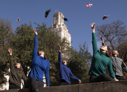 Graduates in front of the UT Tower throwing masks in the air like graduation caps