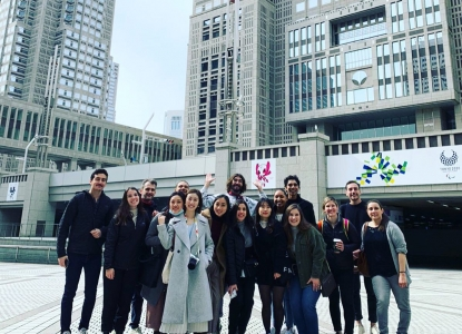 A group of students and Adam Miller smile at the camera as a group, standing on a plaza in front of two office buildings in downtown Tokyo