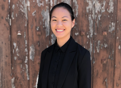 Xie Maggie Hill in all black smiling at the camera against a rustic wood background