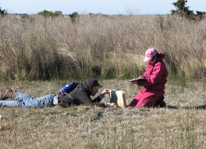 Kelley Russell and Josh Conrad completing a conditions assessment of a grave marker at Cape Lookout National Seashore.