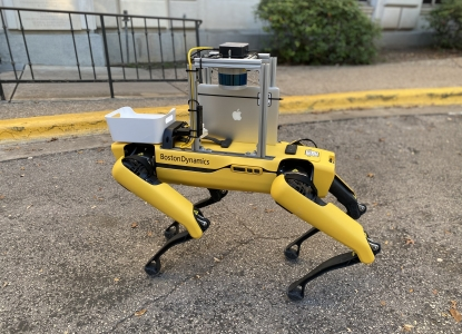 A yellow four-legged robot with an apple ipad attached stands on the sidewalk, poised to deliver cookies on campus