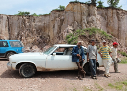 Four Mexican men in hats lean against a white sedan in front of a cliff of brown, rocky cantera stone